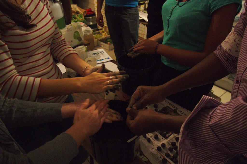 Mains des personnes en train de rouler les boulettes de graines.