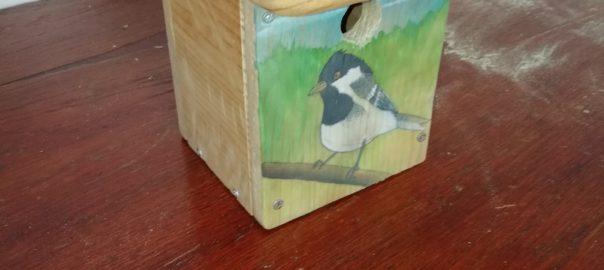 Photo d'un nichoir à oiseaux avec une peinture sur le devant représentant une mésange charbonnière