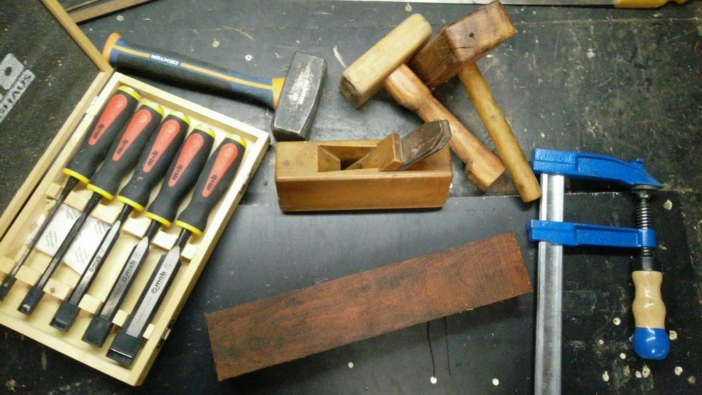 Vue des outils, ciseaux à bois, massette, rabot, maillets, serre-joint et planche en bois.
