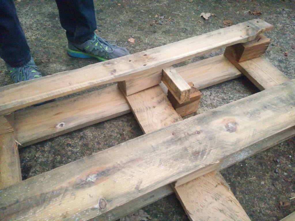 Démonter une palette en faisant levier bavec des cubes et morceaux de bois