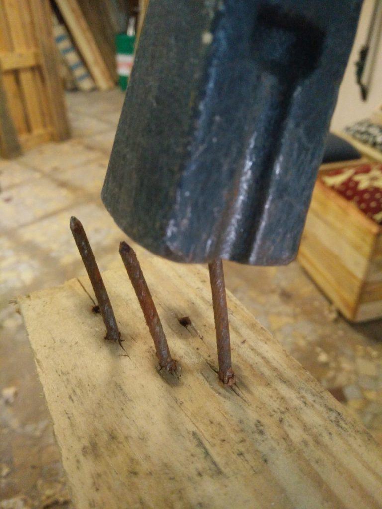 Photo d'un marteau qui frappe la pointe d'un clou pour l'extraire de la planche