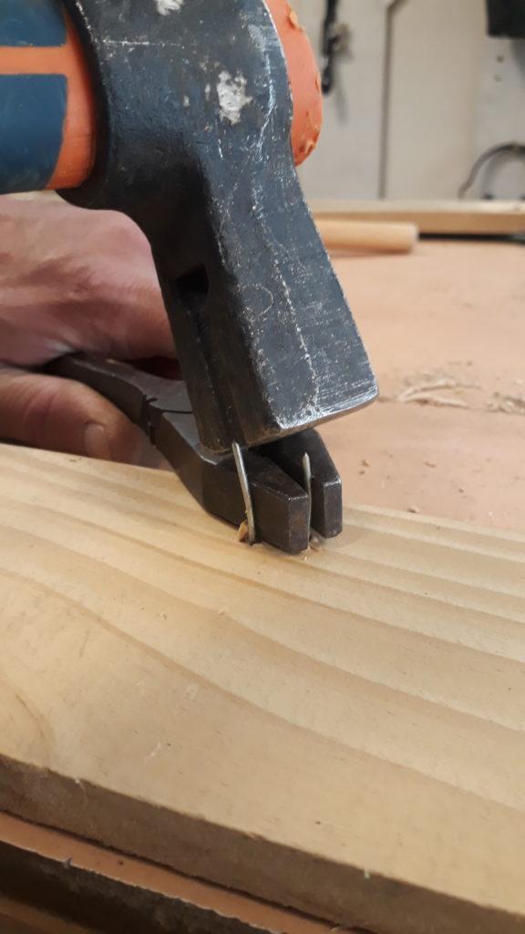 Vue montrant comment tenir une agrafe à l'aide d'une pince plate pour esuite l'extraire avec un marteau
