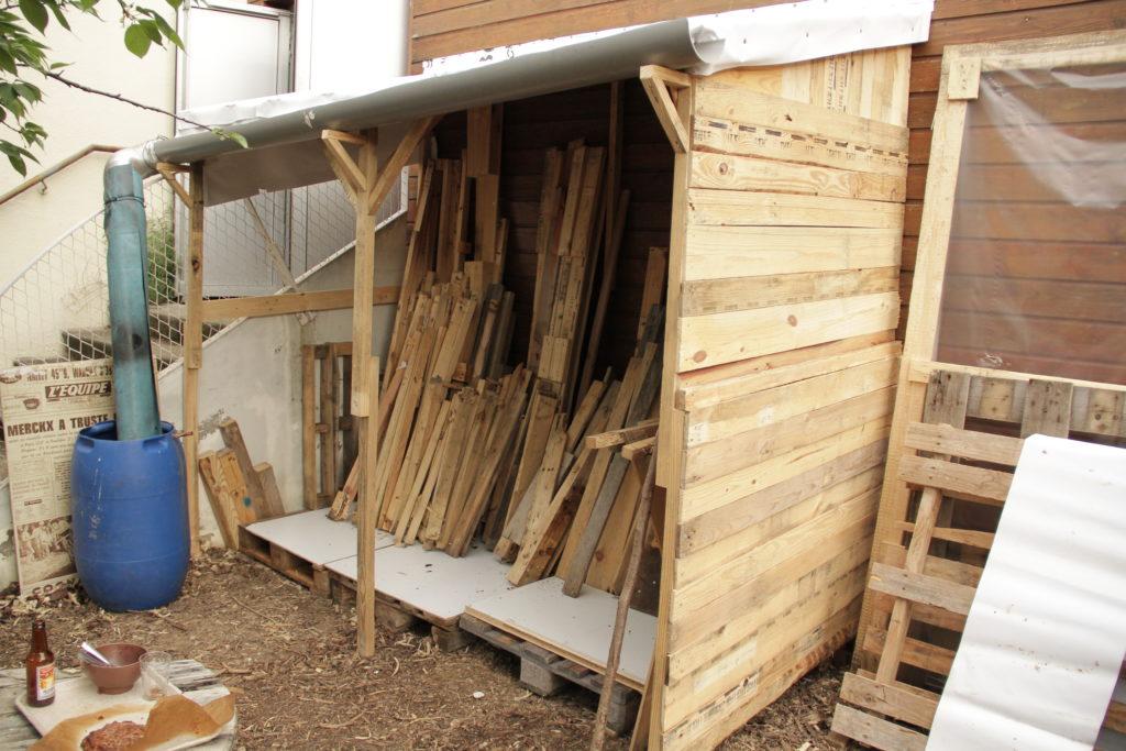 Vue d'un abris réalisé en bois de palettes pour le stcokage du bois