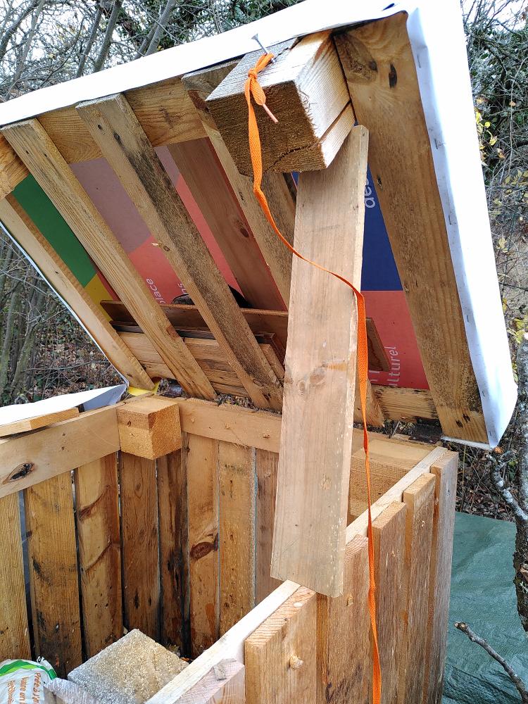 Un  exemple de système permettant de maintenir le toit en position ouverte du bac à compost