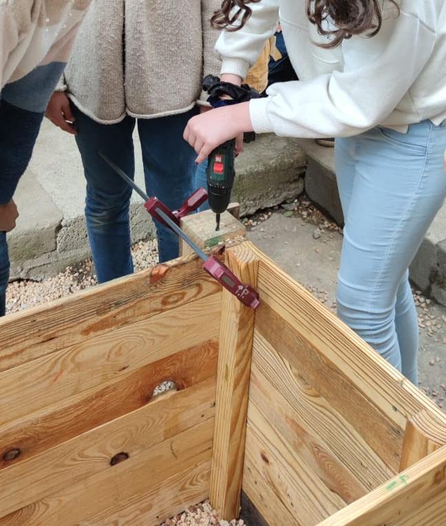 Photo d'un groupe d'élèves en train d'assembler un bac de culure